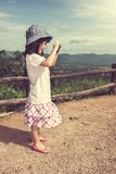 Happy asian girl smiling and relaxing outdoors in the daytime, t. Side view of happy asian girl smiling at view point on mountain and learning take photographs Royalty Free Stock Photo