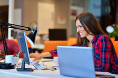 Side view of Happy businesswoman working on her laptop in the office Royalty Free Stock Photos