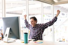 Male graphic designer celebrating success at desk in a modern office. Side view of happy Caucasian male graphic designer celebrating success at desk in a modern royalty free stock photography