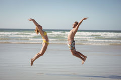Side view of happy couple jumping on shore at. Beach during sunny day Stock Photo