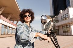 Side view of happy girl in sunglasses posing on motorbike Royalty Free Stock Photo
