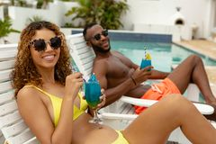 Couple having cocktail drink while relaxing on a sun lounger. Side view of happy diverse couple having cocktail drink while relaxing on a sun lounger near stock photography