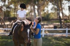 Side view of happy female jockey teaching girl. Horseback riding Stock Image
