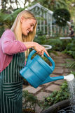 Side view of happy gardener watering plants against greenhouse Stock Image