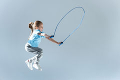 Side view of happy girl humping exercising with skipping rope. On grey Stock Images