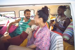 Group of friends having fun in a camper van at beach. Side view of happy group of diverse friends having fun in a camper van at beach stock photos