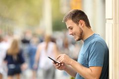 Profile of a happy guy texting on a smart phone Royalty Free Stock Photo