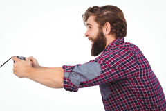 Side view of happy hipster playing video game. Against white background Stock Photography