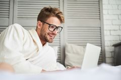 Joyful male using laptop after shower. Side view of happy man chatting with friends online in morning. He is lying in bathrobe and smiling at computer screen Stock Image