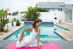 Woman performing stretching exercise near swimming pool in the backyard. Side view of happy mixed-race woman performing stretching exercise near swimming pool in royalty free stock images