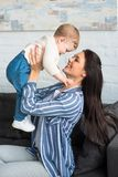 Side view of happy mother with baby in hands sitting on sofa. At home royalty free stock photo