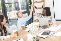 Side view of happy multicultural businesswomen giving high five at workplace. With digital devices royalty free stock image