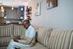 Side view of happy senior man using tablet. While sitting on sofa at home Royalty Free Stock Photo