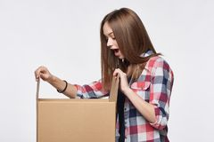 Side view a girl opening a box Royalty Free Stock Image