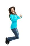 Side view happy woman jumping with thumbs up Stock Photo