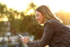Profile of a happy woman using a smart phone in a balcony. Side view of a happy woman using a smart phone in a home balcony at sunset Stock Photography