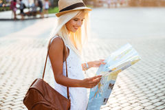 Side view of a happy woman on vacation with map Royalty Free Stock Images