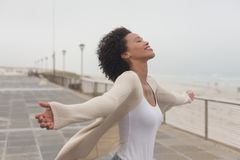Young African American woman with arms stretched out standing at promenade. Side view of happy young African American woman with arms stretched out standing at stock images