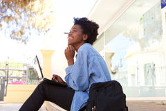 Side view happy young afro american female student sitting outside with laptop Royalty Free Stock Photos