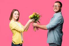side view of happy young couple holding bouquet and smiling at camera isolated