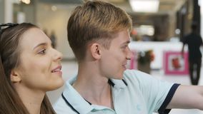 Side View Happy Young Couple Sit and Joyful Girl Talks. About fashionable things in store and guy looks stock footage