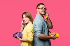 side view of happy young couple standing back to back and talking by rotary phones isolated
