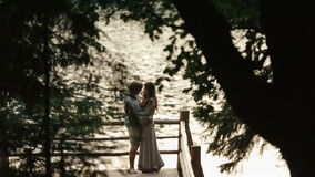 Side view of happy young couple standing on edge of pier by lake in mountains. Carpathians, Ukraine stock video footage