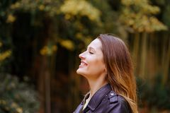 Side view of happy young lady keeping eyes closed and smiling. While standing on blurred background of park trees royalty free stock photos
