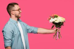 side view of happy young man holding bouquet of flowers isolated
