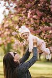 Side view of happy young mother holding baby girl in her hands and looking at her with love royalty free stock photography