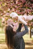 Side view of happy young mother holding baby girl in her hands and looking at her with love royalty free stock images