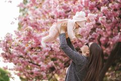 Side view of happy young mother holding baby girl in her hands and looking at her with love stock photo