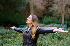 Side view of happy young woman keeping eyes closed and smiling. While standing on blurred background of park trees stock photos