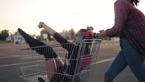 Side view of a happy young woman pushing a grocery cart with her girlfriend inside in the parking by the shopping mall. During sunset. Slowmotion shot stock video footage