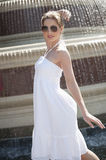 Side view of happy young woman in white halter neck dress standing by water fountain Stock Photography