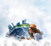 Creative inspiration of young female writer. Side view of hard-working female writer using typing machine while sitting at the table with panoramic Earth view royalty free stock image
