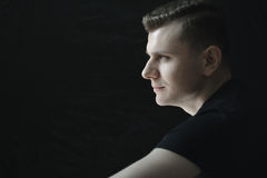 Side view head and shoulders young man portrait in low-key lighting. Side view head and shoulders young man portrait in low-key studio lighting royalty free stock photography