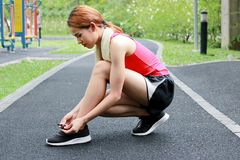 Side view of healthy Asian woman tying shoelaces on running shoes on the street. Fitness and workout wellness concept. Side view of healthy Asian woman tying stock photography
