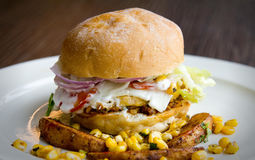 Side view of a healthy egg burger with mayo, corn, potato wedges and more Stock Photos
