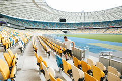 Side view of a healthy male runner in sport clothes. Running upstairs at the stadium Royalty Free Stock Image