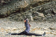 Side view of a healthy mature woman figure stretching and exercising on a rock platform Stock Image