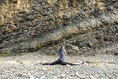 Side view of a healthy mature woman figure stretching and exercising on a rock platform Royalty Free Stock Images