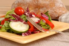 Side view of a healthy salad on a yellow plate with rustic bread
