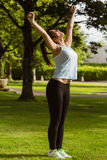 Side view of healthy woman stretching hands in park Stock Images