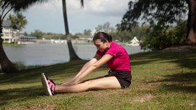 Sportive woman doing stretching exercise on lakeside stock video