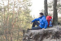 Side view of hiker sitting on edge of cliff in forest Royalty Free Stock Image