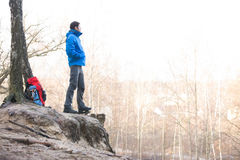 Side view of hiker standing on edge of cliff in forest Royalty Free Stock Photography