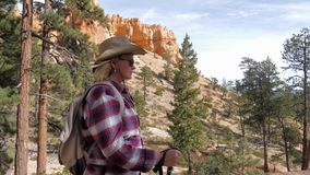 A Side View Of A Hiker Woman Walking Forward In The Bryce Canyon Rocks And Pines. A blonde hiker woman in a cowboy hat, black sunglasses, a plaid shirt with stock footage