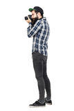Side view of hipster in plaid shirt and baseball cap taking photo with dslr camera. Full body length portrait isolated over white studio background Stock Photo