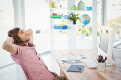 Side view of hipster relaxing at computer desk Stock Image